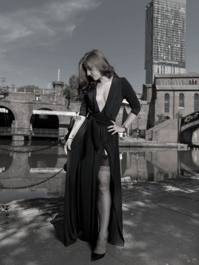 Manchester Dominatrix Mistress Lola Ruin stands by the Manchester Canal system in a long blue gown and stockings