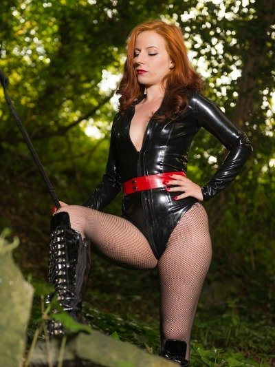 A beautiful Manchester Dominatrix poses in black latex bodysuit with a BDSM crop in a secluded Manchester wood